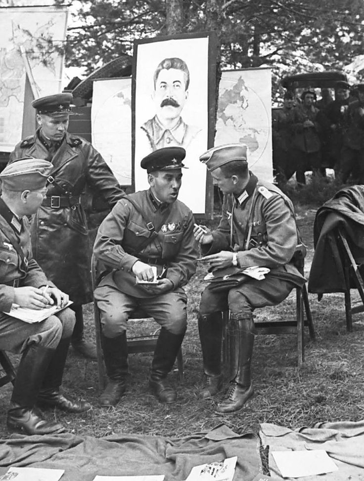 """""""Soviet and German officers meet at the demarcation line, following their joint invasion of Poland"""" (Portrait of Stalin in the background) Photo credit: Bundesarchiv (Germany) Poland, 1939"""