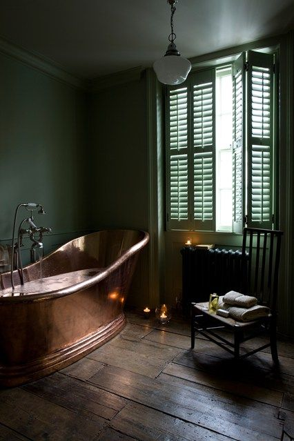 Decorating with dark paint doesn't mean you'll end up with a room of Stygian gloom. In fact the very opposite. Used properly drama and atmosphere await. Like this bathroom with green walls and a copper bath.