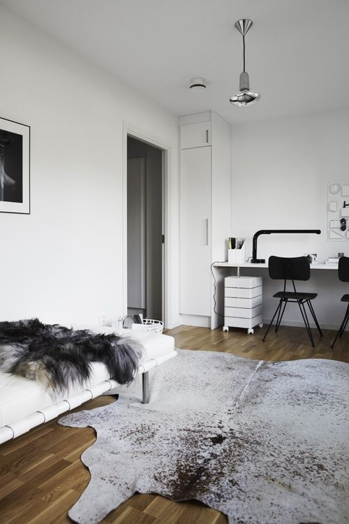 Méchant Design: cow rugs  Downstairs with a black leather couch