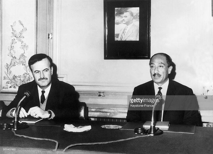 السادات وحافظ الأسد وبينهما صورة جمال عبد الناصر Syrian Prime Minister and Defense Minister Hafez al-Assad with Egyptian president Anwar Sadat on a meeting, at that time the Arab Republic of Syria had just joined the tripartite arab federation formed by Egypt, Sudan and Libya, on December 4, 1970 in Libya.