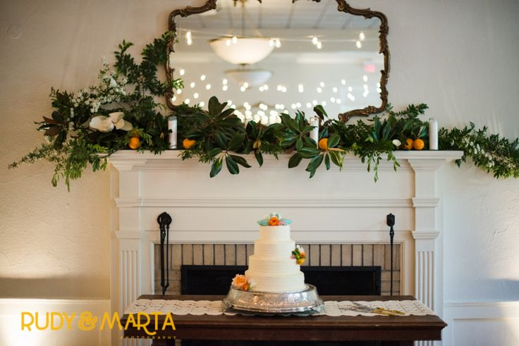in a historic hall, the fireplace mantle is dressed for the reception with magnolia, elm, lemon leaf, fresh citrus, spirea and candles. the wedding cake is centered on an antique table and adorned with peach roses, orange ranunculus, white scabiosa, larkspur buds and fresh calamondin.