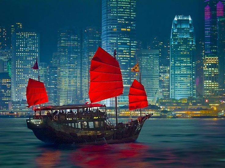 """Hong Kong's historic """"junk boats,"""" recognized by their bold red sails, once carried treasures across the sea but now can be hired for tours. The ships represent the traditional values still present in this cosmopolitan Chinese city."""