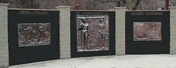 Memorial dos Mineiros de Antracite da Pensilvânia. Relevo em bronze. Zenos Frudakis (São Francisco, Califórnia, USA, 1951 - ). Encontra-se no Parque Girard em Shenandoah, Pensilvânia, USA. São 3 painéis de bronze. Homenageia os milhares de mineiros de carvão, trabalhadores corajosos que viveram e trabalharam na região de antracite da Pensilvânia, e ajudaram a construir a América. O monumento é cercado por tijolos que caracterizam os nomes de muitos dos mineiros, e bancos para descanso.