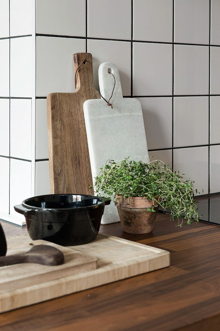 Köket har vitt kakel med svart fog