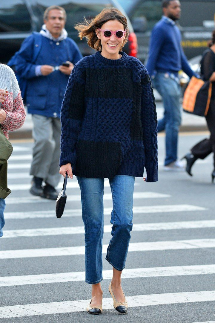 Alexa Chung in a navy cable knit sweater, jeans, flats and pink sunglasses.