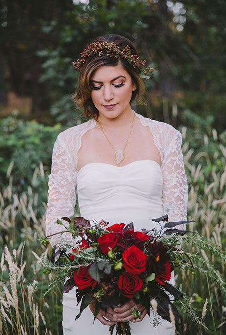 Brides.com: . A winter wedding bouquet comprised of red roses, rosemary sprigs, and deep-hued greenery, created by Florals by Flory.