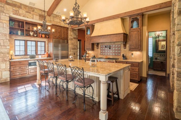 This inviting kitchen features a spacious island with neutral cabinets and a granite countertop. Wrought iron candelabra chandeliers hang above, while neutral stone blocks provide accent walls. Hardwood floors complete the look of the space.