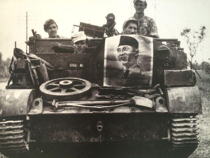 Serdadu Belanda memperlihatkan foto Presiden Soekarno yang disita dari rumah yang dicurigai sebagai gerilyawan Indonesia. Lukisan tersebut dibuat berdasarkan foto Mendur bersaudara. Cirebon, 27 Juli 1947. (Koleksi Museum Bronbeek).