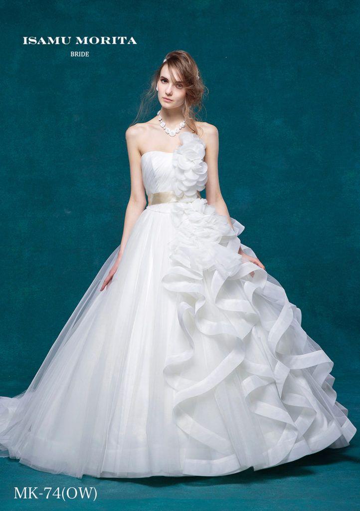 MK-74 - ISAMU MORITA ウエディングドレス - 胸元からスカートへと流れるようにつながるフリルが圧倒的な美しさを醸し出すドレス。 流行の幅広パイピングラッフルは花嫁様の後姿まで多くの人を引き付ける優雅さ。身頃の繊細なタック、チュールスカートとフリルとの対照的な対比も印象的なドレスです。 アシンメトリーとローウエストが重なったモダンビューティーなドレスです。