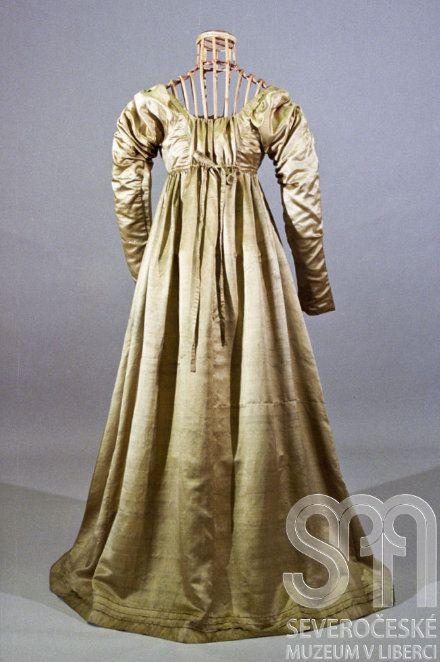 Dámské empirové šaty ručně šité ze světle olivově zeleného hedvábného atlasu. Šaty mají čtvercový výstřih s obvodovým tunýlkem provlečeným šňůrkou na zavazování. Vzadu v trupové části šaty rozstřižené a pod hrudníkem opatřené stuhou na zavazování. Rukávy dlouhé v horní části zdobené nabíráním. U spodního okraje manžet a sukně ozdobně šité sámky. Rukávy a částečně i živůtek podšity bavlněným plátnem. Ke spodnímu okraji sukně našita lemovka.