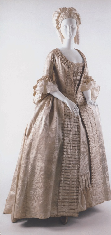 Robe a la Francaise, 1770, ivory silk damask. The dress has a watermelon colored lining - a textile that has been recycled. (c) Metropolitan Museum of Art.