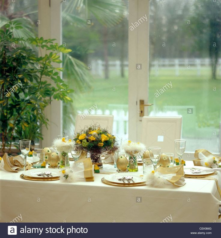 Tablesetting: Easter Dining Table laid, cream tablecloth, gold ribbon runners, pile of white and gold plates.