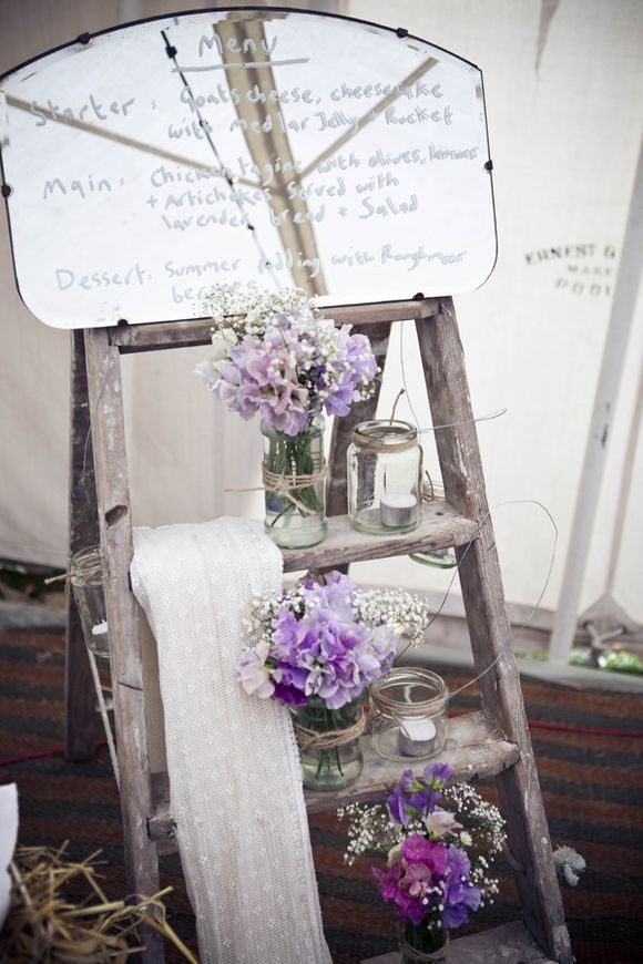 Wedding menu written in white on an antique mirror & vintage inspired props with purple flowers...: