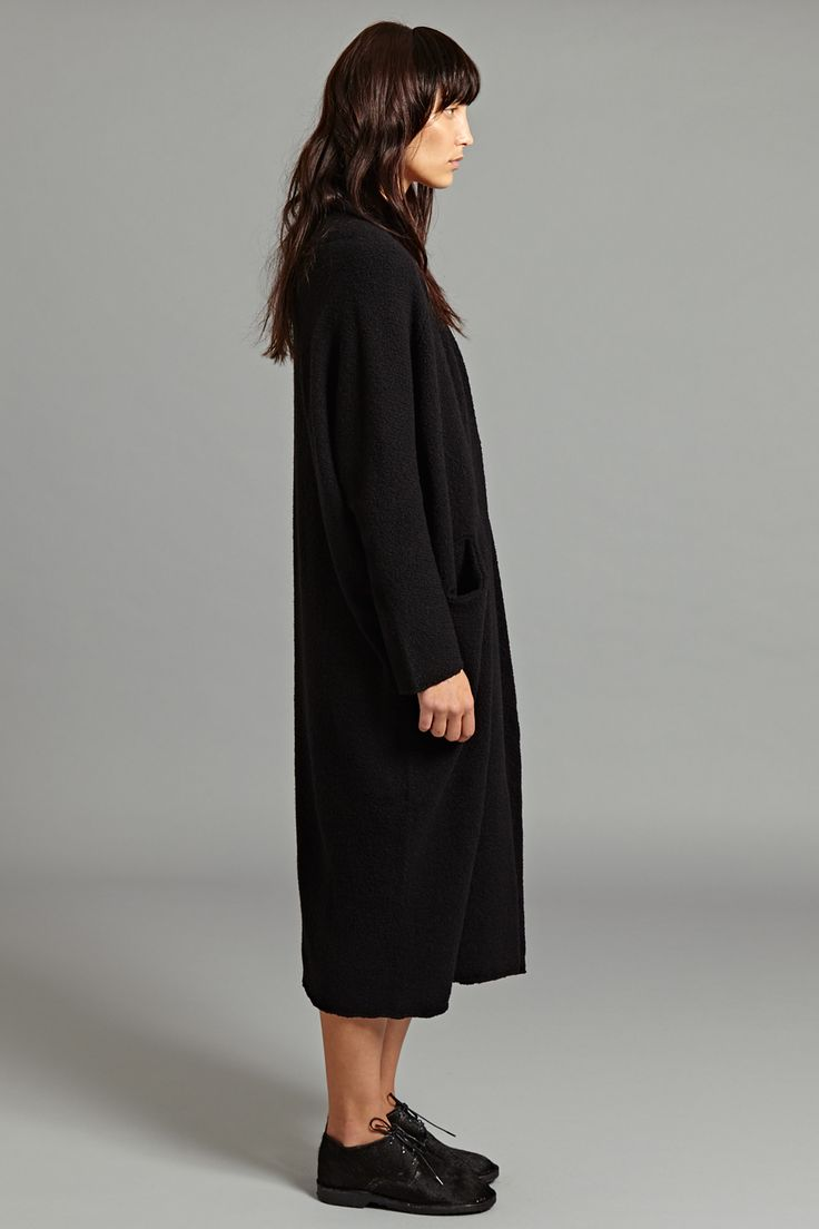 Luna Coat in Black. The boucle texture of this knitted cashmere coat brings an unexpected touch whilst retaining the softness of its wool/cashmere fabric. The coat features a 'pod-like' silhouette with a draped shoulder construction. There is a subtle pocket on either side at waist level.