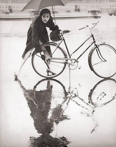 bicicletta con donna nella pioggia con ombrello