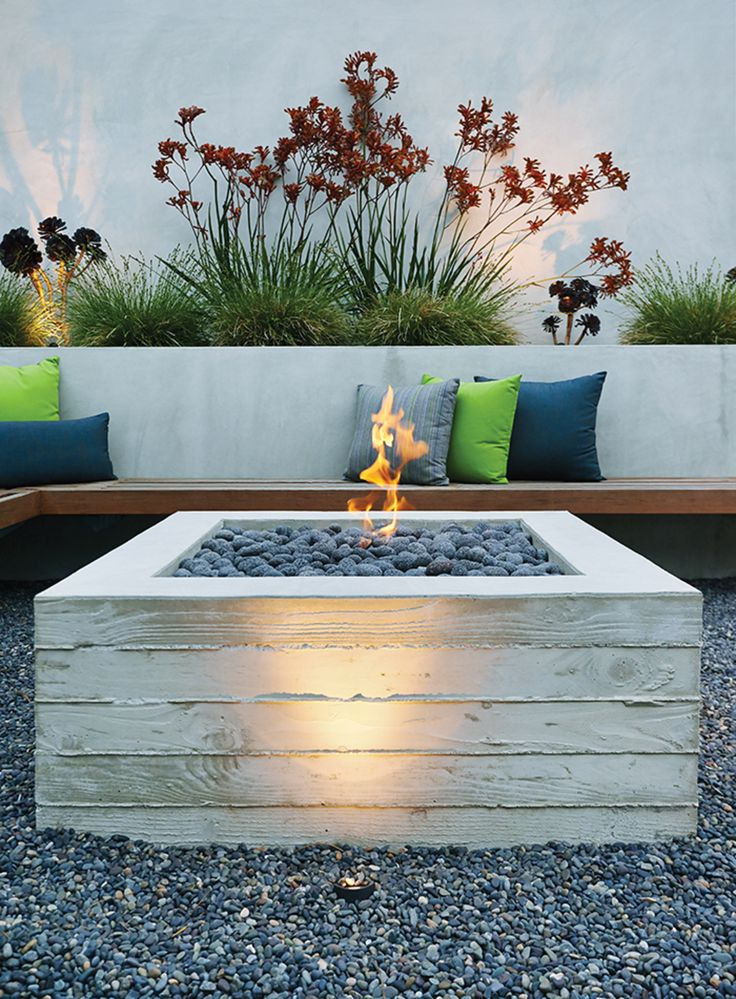 A cantilevered ipe bench hugs a custom board-formed concrete fire pit.