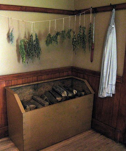 A woodbox and herbs drying on the line.