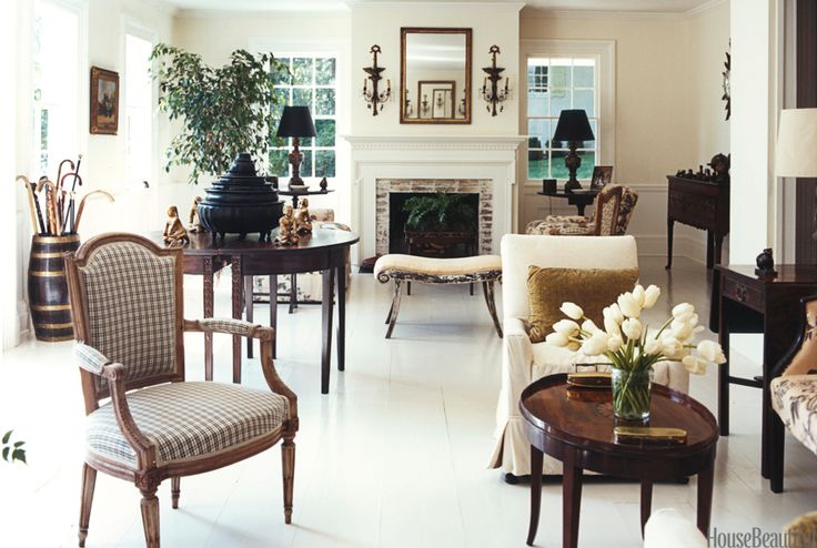 """In the living room of the same house, Hadley took a somewhat minimalist approach. """"When you're working on a small-scale house or apartment, simple is always better,"""" he said. He painted the walls in a clean white; the pine floors received a coat of cool gray. Like exclamation points, black lampshades punctuate the windows at the far end of the room.   - HouseBeautiful.com"""