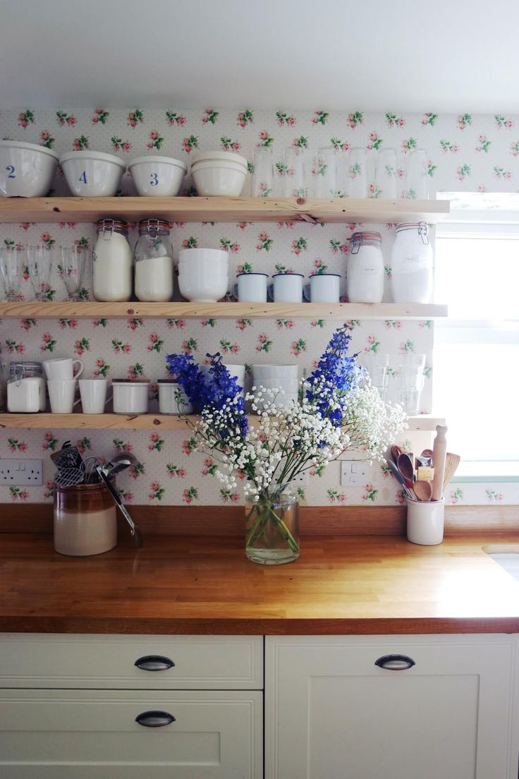 We don't often see a sweet floral wallpaper like this one paired with streamlined floating shelves — but we sure do like it.