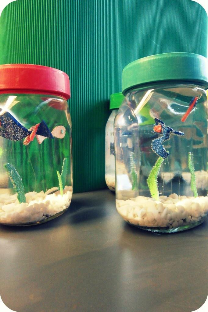 Mini aquarium. Leuk om tijdens de feestavond te maken, samen met wat ouders. Plastic potjes verzamelen, plastificeer apparaat bij de hand, wat aquarium steentjes in verschillende kleuren verzamelen, rietjes en knutselen maar.