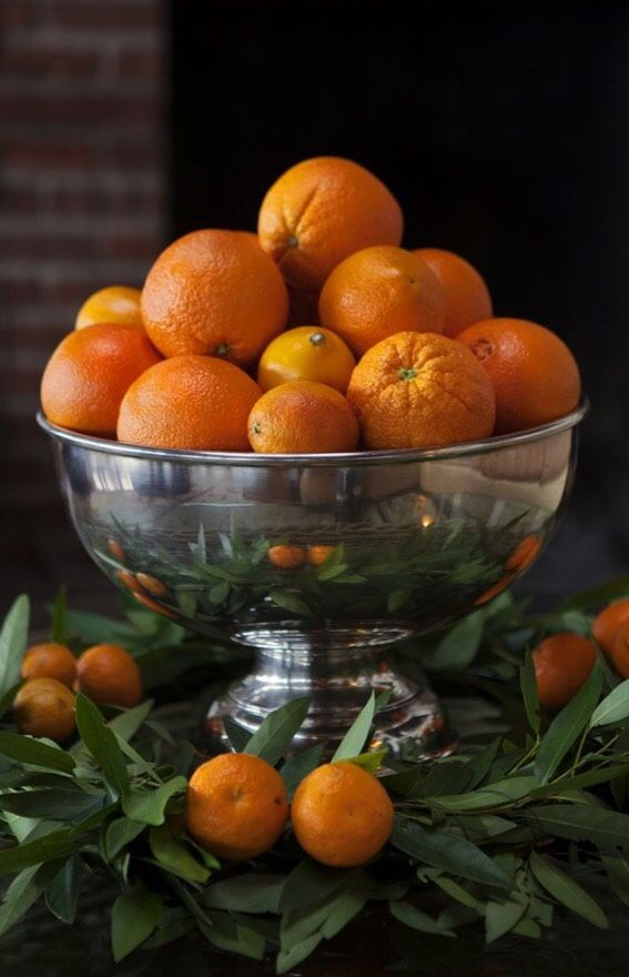 Holiday Centerpiece ~ Festive, easy to achieve. Use a silver punch bowl, a green wreath, and a variety of oranges to dress up your table.