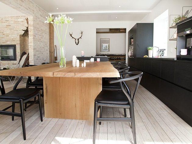 Et helsvart kjøkken kombinert med lunt treverk, eksponert mur og hvite vegger gir kontrastene som trengs for å skape et varmt og innbydende rom.