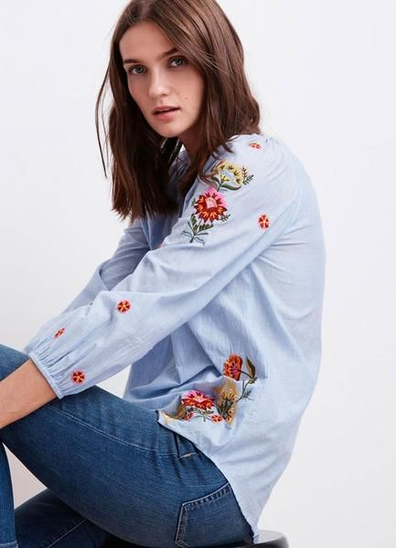 Simply pretty, this cotton chambray peasant top features floral embroidery down the sleeves and at the hip. An easy shape with full sleeves and a scooped hem. 1