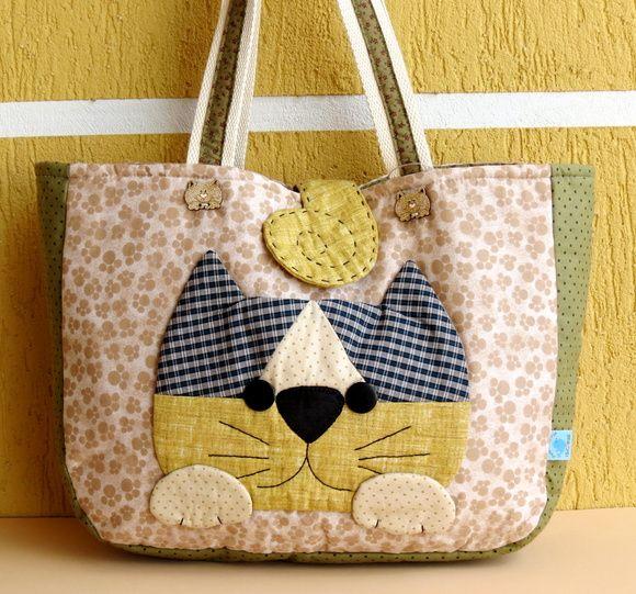 Bolsa do gato sorrateiro, feita com a técnica foundation (é uma técnica milenar de patchwork, em que os tecidos são costurados sobre uma entretela, seguindo um risco e uma ordem exata). Os detalhes de boca, bigode, patinhas e cauda são bordados à mão. O fecho é em botão imantado. R$ 115,00