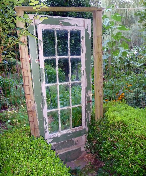 old french door as gate-between boxwood hedge very fitting