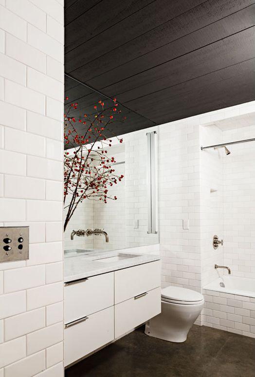 Dark ceilings contrast this sleek white bathroom
