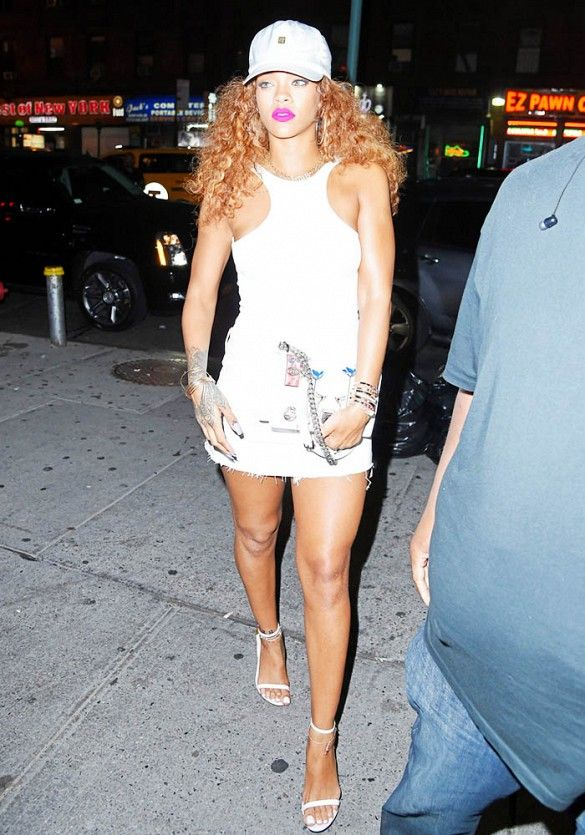 Rihanna in an all-white ensemble including a baseball cap, dress, and heels.