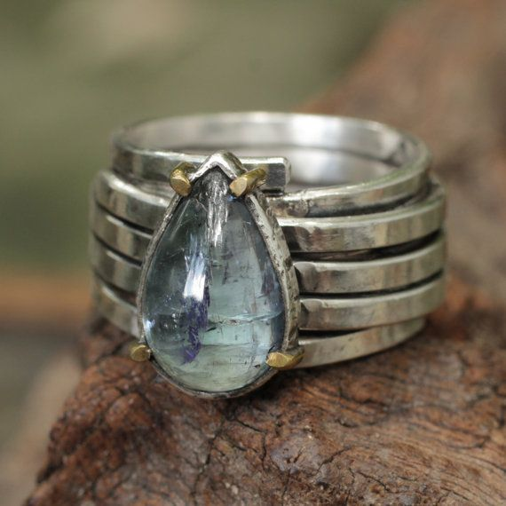 Blue kyanite gemstone in oxidized silver bezel setting with brass prongs and multi band
