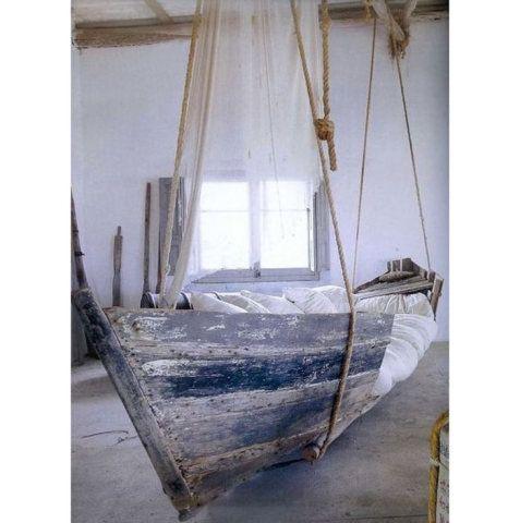 Feita dentro de um antigo barco, esta espaçosa cama combinou madeira e roupa de cama branca. Uma viga no teto sustenta tudo com cordas.