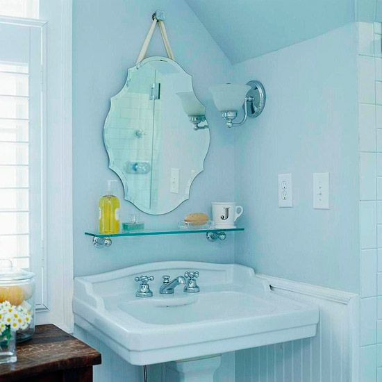 This pretty bathroom has been updated with a glass shelf and a statement mirror.