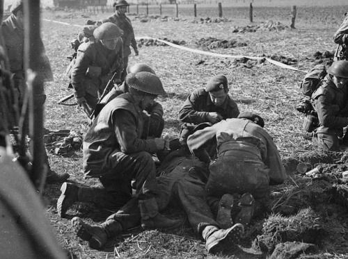 Regimental Aid Party treating a infantryman of The South Saskatchewan Regiment who was wounded by sniper fire while crossing a canal north of Laren, Netherlands, April 7, 1945.
