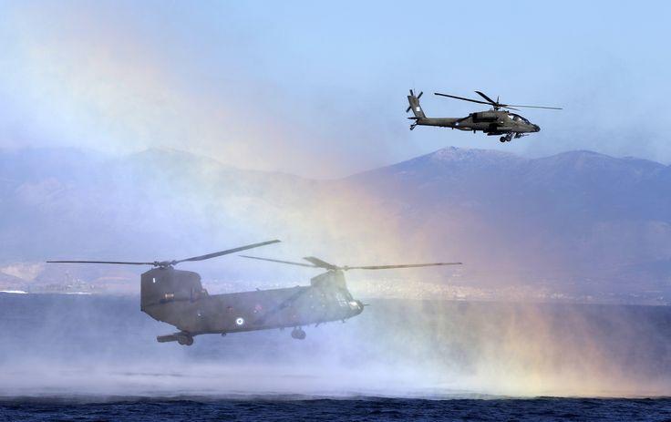 Pelangi muncul saat helikopter NATO berpartisipasi dalam latihan militer 'Pyrpolitis' di Teluk Saronic, selatan Athena, Yunani.