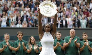 Applause rings around Centre Court as Serena Williams holds the Venus Rosewater Dish aloft.