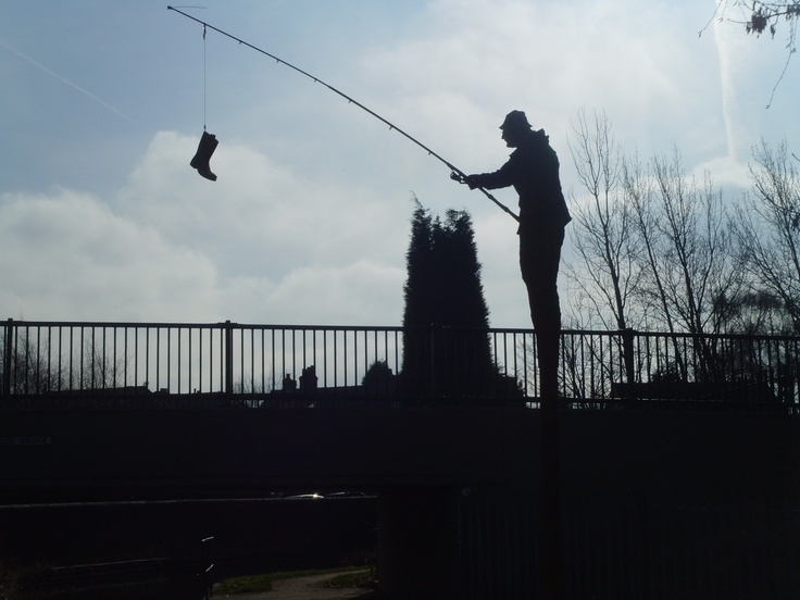 Morris the fisherman, Walsall wood street art , on Canal Towpath. Fish replaced with welly by someone.