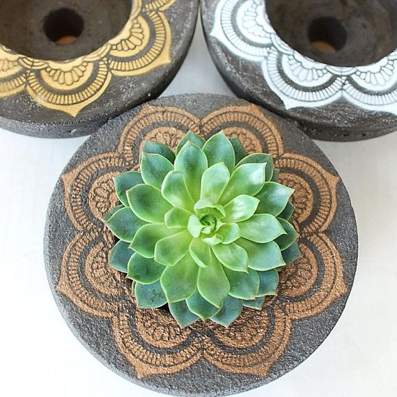 This round concrete planter is handmade and adorned with a painted mandala. The mandala is a geometric figure representing the universe and