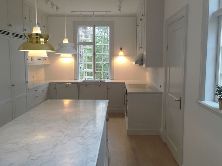 Light gray kitchen with Carrara Marble kitchen island and counter tops
