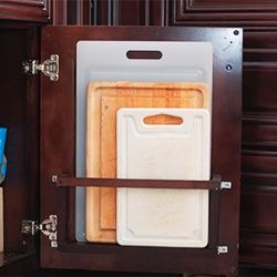 Cutting board holder that hides behind a cabinet door