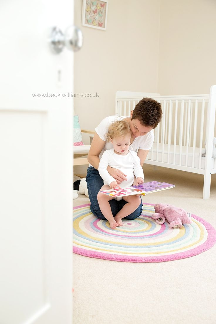 Family photography - mum and baby reading in the nursery.  I love the whiteness with the pop of colour from the blanket and book.