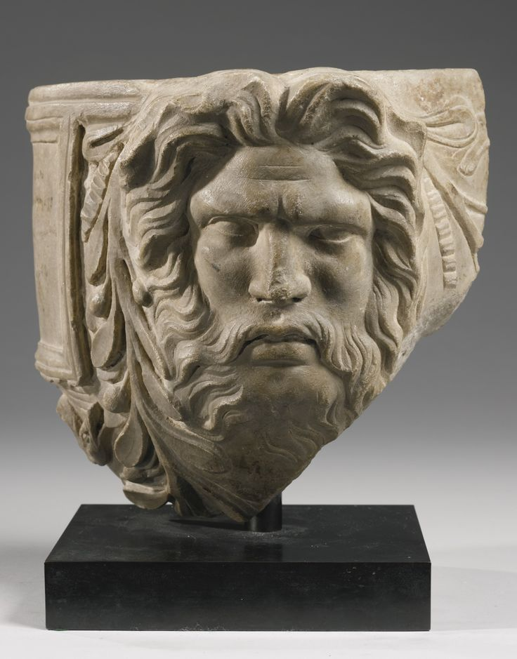 "A ROMAN MARBLE CINERARY URN FRAGMENT, 1ST CENTURY A.D. carved with a fragmentary recessed panel above a serpent's head, and with the head of a bearded deity with long radiating hair swept up above the forehead, an olive garland tied with a ribbon falling on both sides of the head, the panel inscribed in ink in a 19th Century hand: ""Scavato il 10 Marzo 92 [.......] Spoleto."" Height 8 1/2 in. 21.6 cm."