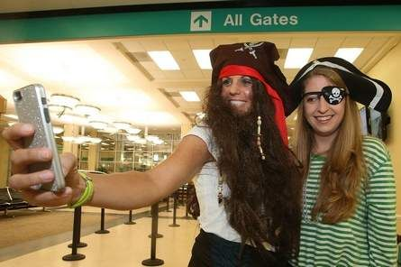 Leslie Sloan, left, and Amy Noll take a photo of themselves after signing up for the Allegiant Air International Talk Like a Pirate Day photo scavenger hunt at Asheville Regional Airport on Friday. Contestants had to get photos of themselves at various locations around Asheville for the chance to win tickets to Florida. Photo from MIKE DIRKS/TIMES-NEWS