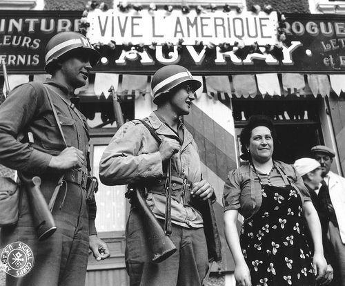 Au Molay-Littry rue de Balleroy, Mme Auvray pose avec deux MP. (Conseil Regional de Basse-Normandie / National Archives USA).