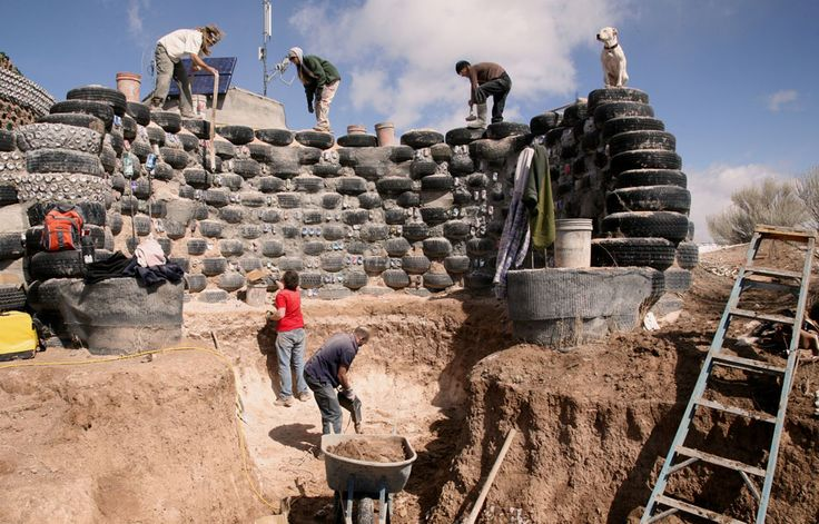 Building retaining walls of an earthship with old tires ...