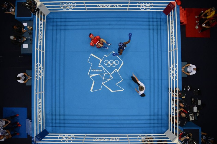 Cancan Ren of China (in red) is knocked down by Nicola Adams of Great Britain (in blue) during the women's boxing Flyweight final of the 2012 London Olympic Games.