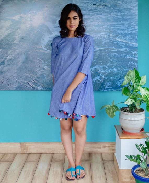 This flared swing dress is crafted from handwoven khadi cotton fabric and detailed with over 100 multi-coloured block printed handmade pompoms lining the hem.