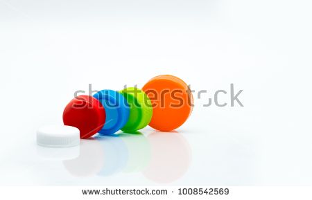 Macro shot detail of different size of white, green, red, blue and orange color round plastic screw caps on white background and copy space.