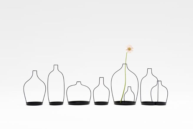 nendo design japan thin black vase for David Design A vase collection based on the 'thin black lines' concept premiered at the Saatchi Gallery in London in 2010. The collection consists of eight forms: a bottle, a tumbler, a coffee mug, a teacup, a wine glass, a pitcher and a bowl. Users pour water into a small vial of water, then place the flower inside. The result: a silhouette that magically supports a flower.